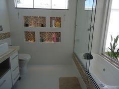 No banheiro desta casa em Jardim (MS), as pastilhas de vidro em tons ferrosos nos nichos, nas faixas horizontais e na borda da banheira dão o toque colorido ao ambiente. O porcelanato branco no piso e nas paredes também formam o espaço, de 2,05 x 2,60 m. Uma janela alta e uma janela baixa, no nível da banheira, possibilita a integração com o jardim privativo da suíte. O projeto é assinado pela arquiteta Bianca Monteiro.CasaPRO: 32 banheiros coloridos para sua casa ou apartamento - Casa