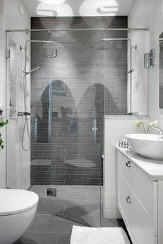 """Zestawienie na ścianach dwóch różnych """"cegiełek"""" dało niewątpliwie dekoracyjny efekt w tej łazience. W kabinie prysznicowej, która zajmuje całą szerokość pomieszczenia, zainstalowano szklane drzwi bez profili, podwieszane na rozpiętej między ścianami szynie. Elegancji wnętrzu dodają szafka ze stylowymi uchwytami i marmurowe elementy – blat pod umywalką oraz wykończenie gzymsu i wnęk pod prysznicem."""