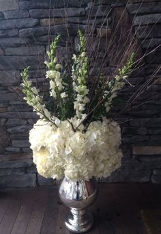 Mercury vase urn with collar of white hydrangea, white snaps and birch branches standing tall. Makes any escort card table look great!