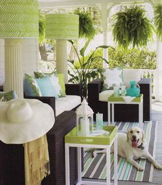 Great porch...love the pillar floor lamps and of course the neat green fabric, used for shades, by Alan Campbell.  Love that lime green tray table too.