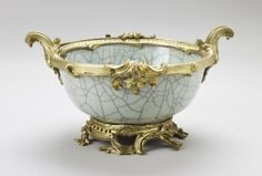 """1740 French Bowl in the Royal Collection, UK - From the curators' comments: """"This [Chinese] bowl (which has an accompanying vase) was made circa 1730-40. The gilt-bronze French rococo mounts are thought to be from the middle of the 18th century. This thickly-potted bowl is decorated with a glazed near-white broad crackle pattern. The foot ring is encased in a gilt metal band with rococo scroll feet."""""""