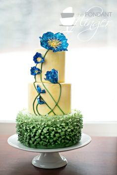 Blue Poppy Cake  By: FondantFlinger  Ombre green grass ruffles covered the bottom tier. Two yellow tiers brushed with gold dust and highlighted with bright blue poppies. I designed this cake to look like flowers in a painting.