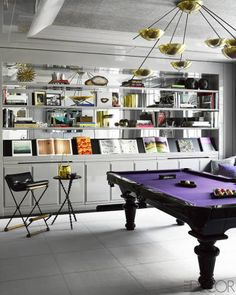 A chandelier by Stilnovo and a felt rug by Stark in this billiards room.