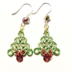 Christmas tree earrings made with Japanese Chainmaille weave. Made with green and red rings, silver and gold rings. earhooks are silver plate non tarnish wire with a metallic purple Rondelle bead. Christmas Tree Earrings, Cute Christmas Tree, Wire Earrings, Drop Earrings, Earring Tree, Chainmaille, Gold Rings, Jewelry Making, Jewels