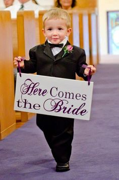"Purple wedding ideas. A sign that says: ""Here comes the bride"""