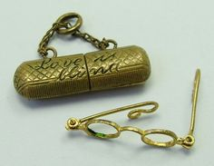 An Edwardian c1910 brass glasses case with 'Love is Blind' on the outside that opens to reveal the tiniest pair of fully removable & articulated spectacles inside.