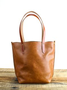 This handmade Horween leather tote bag is an instant classic. Its the perfect bag to take you from work to errands to weekend. Big enough to stash all your everyday items (including your small laptop or ipad), but small enough to be light and easy to carry. We hand cut buttery soft yet durable 4oz Horween Natural Dublin and stitch it with heavy weight nylon thread. The handles are made using Wickett and Craig bridle leather in three color options, and riveted with antique brass rivets. The…