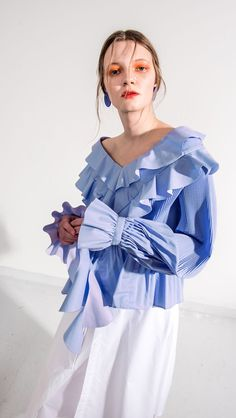 The Dahlia Top in Blue. With ruffle cuffs and front detailing in pleated sleeves. Can be styled as backwards. COMPOSITION AND CARE Dry Clean Please treat with care to extend the life of your cloth 60%