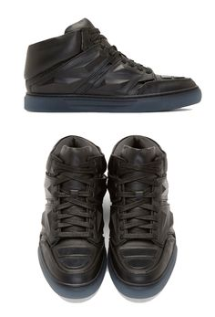 Black Leather Exotron Sneakers by Alejandro Ingelmo. Mid top leather sneakers in black with round toe with patent plastic accent panels. Black lace up closure, accent straps at sides with tonal raised prism details. Translucent blue rubber sole. http://www.zocko.com/z/JJKXv