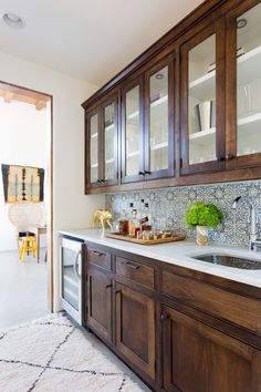 Rich wood cabinets line the bar, which also features a backsplash of Ann Sacks concrete tile.