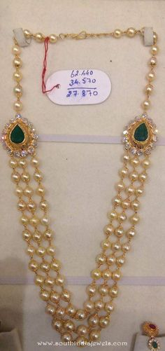 22k gold long parl haram with side locket studded with white stones and emeralds. For inquiries please contact the seller below. Seller Name : Dhanlaxmi Jewellers Contact No : 9059102044 More CollectionsGold Antique Multi layer Long Necklace SetGold Pearl Emerald Mala from Dhanlaxmi JewellersTraditional Pearl Long Haram DesignGold Long Haram with Floral PendantGold Long Pearl