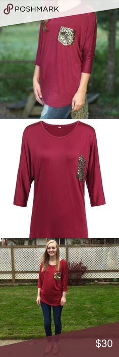 """Maroon/Burgandy Shirt With Sequin Pocket Beautiful vibrant maroon/burgundy color with Sequin gold pocket. I think it is a rayon/Polyester material it feels kinda like loose spandex. The sleeves are three quarter length. The top is very loose and flowy.  The label says size medium but fits a small better. In the third picture I am a size small wearing a medium. Length 28"""" From underarm to underarm 23"""" because it is very loose and flowy. Tops Tees - Long Sleeve"""