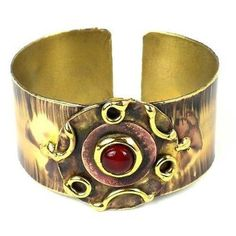 Carnelian Medallion Copper and Brass Cuff Handmade and Fair Trade. Handcrafted by South African artisans, this cuff features a disc of brass with a center of copper and a carnelian stone. The color on this 1.25-inch bracelet is achieved by applying extreme heat rather than paints or dyes.