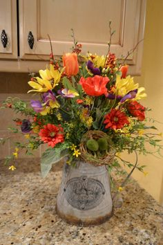 Brighten up your table with this beautiful spring arrangement! It is made in a metal pitcher and is full of beautiful spring flowers with a