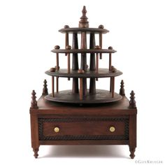 """This majestic sewing stand has a 4-tier spindle with 3 tiers for holding spools of thread. Mahogany with turned finials at each corner and at top of spindle. Cabled wood fillet inset on drawer front with pair of turned bone handles. Part of Glee's collection for over 45 years. Early acquisition that has been a feature in her office since the '70s. DATE:1870-1880 SIZE:9.25"""" x 9.25"""" x 13.5"""" CONDITION:Very Good. No chips or wood loss. Some surface dings to edges of tiers. Missing 2 pins. Spool Holder, Thread Spools, 45 Years, Sewing Box, Drawer Fronts, Glee, Corner, Chips, Surface"""
