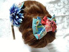 着物帯の変わり結び;二重奏結びを型どったヘアアクセサリーとダリアの花をセットにしたヘッドドレスです。着物帯結びを型どったアクセサリーは珍しく、和装の時には実際の帯結びと合わせてもお洒落感が増すのではないかと思います。薔薇と桜柄で華やかな印象です。クリップを使用することで、ショートヘアにも飾って頂けると思います。共布でダリアのアーティフィシャルフラワーの髪飾りをセットにしています。成人式や卒業式、和装婚、パーティーなどを華やかで上品に彩ってくれると思います。着物帯結びアクセサリーは、和装はもちろんですが、普段の日常生活の中でも、差し色となり、普段遣いをして頂けると嬉しく思います。十分に気をつけておりますが、稀に接着剤のはみ出しがあるものが御座います。また、写真の撮り方により色彩のイメージが若干違う場合があります。ご了承の上、ご注文頂きますよう御願い申し上げます。