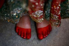 A foot of a Newar girl is pictured during a ceremony in Kathmandu. In the ceremony, girls are married to Bel, the fruit of a wood-apple tree, before reaching puberty. A Newar girl will be married thrice in her life, first to Bel, a second time with the sun in another ritual, and lastly with her future husband later in life