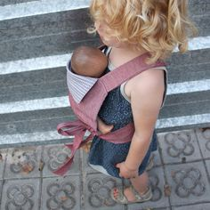 A baby doll carrier.  Only instructions are:   * A square (lined): 24x26cm * Bottom strap with velcro fastening - about 7cm wide and long enough to overlap at the back. * Shoulder straps about 5 cm wide and quite long 110 sewn in at an angle * Head piece (lined): Measured to fit in the space between the 2 straps at the top. Sides cut at an angle.