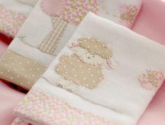 As Fraldinhas de Boca são bordadas à mão com desenhos da Ovelhinha e suas borboletinhas. Feitas em algodão, têm barra de tecido floral e detalhes cor de rosa, tema da coleção. São 03 unidades de 32 x 32 cm cada.