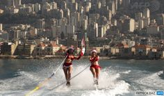LEBANON, Jounieh : Two Lebanese women wearing Santa Claus outfits and waving their national flag water ski during a show in the bay of Jounieh, 20 kms North of Beirut, on December 24, 2013. AFP PHOTO / PATRICK BAZ