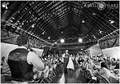 A B&W wide shot of the barn with the bride and groom smiling happily as the best man gives his toast speech at the D-Barn also known as Dickens Barn in Longmont, Colorado. - April O'Hare Photography http://www.apriloharephotography.com #ColoradoWedding #OldMillPark #Longmont #Colorado #LongmontWedding #ColoradoRusticWedding #HistoricSite #RedBarn #DBarn #LongmontBarnWedding #DickensBarn #StringLights