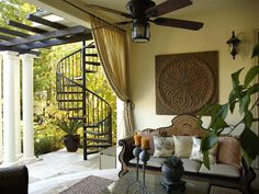 Designer Nicole Yee, of NY Interiors, created this open porch for a client who wanted to enjoy a quiet shady spot. The antique Moroccan furniture was coated with urethane to prolong its life in the outdoors. The outdoor-friendly pillows, cushions and trim are made by Duralee, and the custom draperies are from Sunbrella. An outdoor rug, zinc candleholders, metal art and plantings finish the look.
