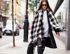 Buffalo check scarf, grey crew neck sweater, collared white shirt, ripped jeans, and black long coat for an effortless look