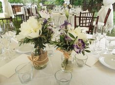 Milk bottles filled with olive branches, peonies and lavender for a Tuscany countyside wedding