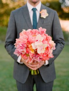 Coral peonies, tea roses, mini phalaenopsis orchids...not sure why the groom is holding it though. Still pretty.