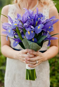 Brides.com: . Iris. The inspiration for the fleur de lis, France's national emblem, the iris represents three important entities: faith, valor and wisdom. It's best known for its deep purple shading.