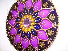 Mandala Móbile em vidro, diâmetro 12cm, técnica pintura vitral em vários tons violeta. Decorada com pedras e bolinhas em acrílico, com suporte de nylon e argola segura para pendurar, finalizada com verniz impermeabilizante que impede o desbotamento do tempo. Embalada em caixa redonda de papelão b...