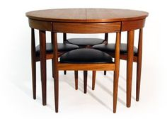 This Danish Modern masterpiece was designed in the 1960s by Hans Olsen for Frem Rojle. Four 3-legged chairs fit snugly with the skirt of the table, making it a perfect compact dining solution for small spaces. Its design is so economical yet almost whimsical, like a 3-dimensional puzzle or game of Tetris.