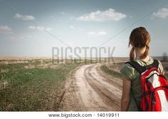 young girl with backpack on road to somewhere