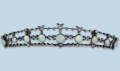 AN ANTIQUE OPAL AND DIAMOND DIADEM The front set with a line of graduated cabochon opals to a foliate framework enhanced with rose-cut diamonds, late 19th century.