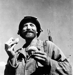 Enjoyment of doughnut by GI on Okinawa is reflected in his all-out smile. Ryukyus. c. 1945. (U.S. Army/National Archives).