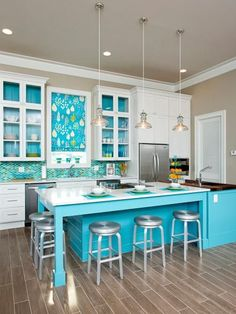 With+a+mosaic+backsplash+that's+reminiscent+of+fish+scales+and+cheery+splashes+of+turquoise+throughout,+it+will+come+as+no+surprise+that+this+kitchen+is+at+the+coast.+The+watery+palette+was+inspired+by+unobstructed+views+of+the+Gulf+visible+from+the+adjacent+family+room.+Although+this+home+is+used+as+a+rental,+the+owners+spared+no+expense+when+choosing+finishes+like+quartz+countertops+complemented+by+a+black+walnut+prep+area+at+the+far+end+of+the+kitchen's+massive+island.