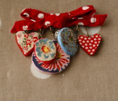 clay charms painted and/or decoupaged with bits of fabric and paper