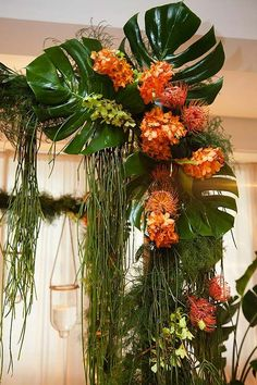 Orange and green orchids, banana leaves and pincushion proteas are draped over the pillars of this tropical-themed altar.