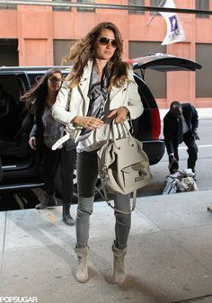 Gisele Bundchen layered up in a white leather jacket, a silk scarf, gray skinny jeans, and gray suede boots in NYC.