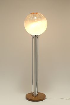 Mazzega, Venezia Italia anni '70.  A floor lamp with wooden base and chrome-plated metal stem surrounded by three slender chrome-plated tubes that are joined to the stem with small balls. The transparent glass globe is opalescent in the lower part. Deep grooves and brown stained glass at the tip of the globe. Characteristic Mazzega production.