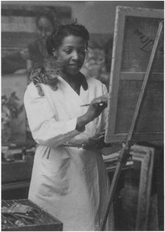 Loïs Mailou Jones painting in her Paris studio in 1937 or 1938, with a kitten supervising from her shoulder.