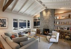 Instead of built-ins, open and airy floating shelves contrast with beams and stone.