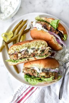 Greek Turkey Burgers with Tzatziki Sauce are packed with fresh spinach, sun-dried tomatoes, oregano and feta cheese for a healthy Mediterranean version for hamburger fans   http://foodiecrush.com