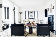 Gorgeous and glam white and black living room space with armchairs, sofa, and marble fireplace