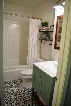Small bathroom remodel with subway tile walls and cement tile look floor tile.