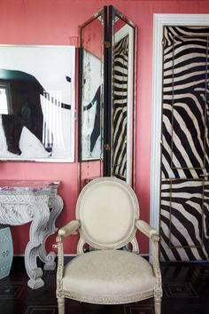 Bold, pink walls, zebra stripes studded door and shiny rustic/worn mirror - very luxe! Designer Miles Redd by Paul Costello featured in June 2013