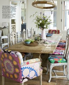 Country Living March 2013 : vintage rustic eclectic artsy style dining room . Suzani fabric covers on silver-painted wood chairs by Redford House and Zentique's armchairs and birch side chairs . pine dining table from Restoration Hardware