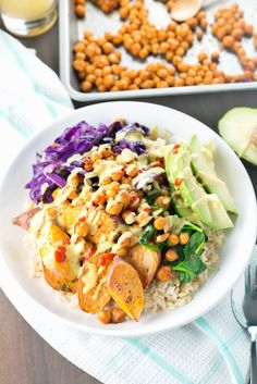 Spicy Buddha Bowl loaded with Brown Rice, Maple Sriracha Chickpeas, Roasted Sweet Potato, Veggies and a creamy Turmeric Tahini Dressing