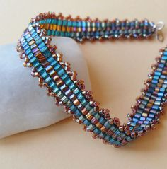 Teal Green and Amber Bead Bracelet. A luxurious striped design with glittering teal green and amber glass beads. I've used Peyote Stitch to sew the beads together, then finished the bracelet with a detail of tiny amber glass beads along the edges.