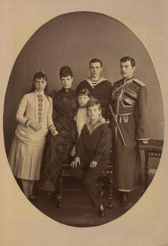 Maria Feodorovna, Imperatriz da Rússia com seus filhos Czarevich Nicholas,o Grão-Duque George Alexandrovich, grã-duquesa Xenia Alexandrovna, Grão-Duque Miguel Alexandrovich e grã-duquesa Olga Alexandrovna. Miguel e Olga estão sentados em uma cadeira de madeira. Maria Feodorovna está em pé ao lado deles para a esquerda usando um vestido escuro. Xenia está em pé ao lado dela para o lado esquerdo. Nicholas e George estão de pé para a direita, com Czarevich Nicholas vestindo uniforme cossaco.Em…